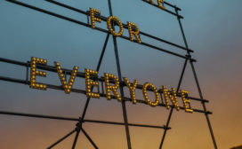 "At dusk an electric sign reads ""For Everyone"""