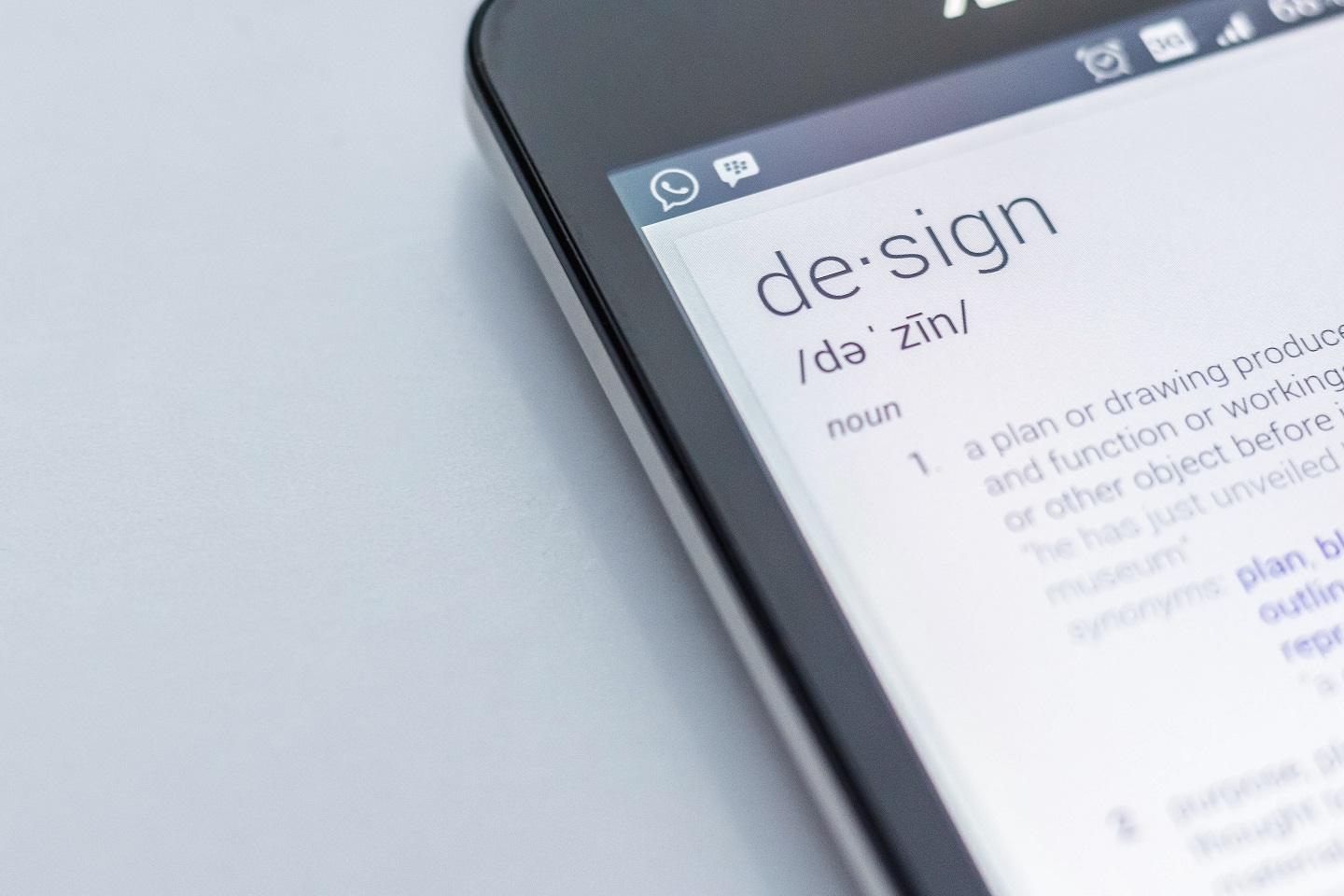 """A mobile device with a screen that shows the pronunciation and definition of the word """"design"""""""