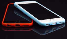 On a black background two smart phones, one on top of the other crossed, the top with a white case, the bottom with a red case