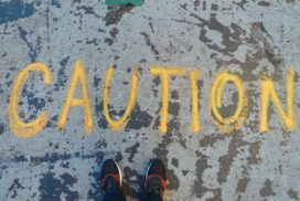 "In yellow the word ""caution"" is written on the pavement"