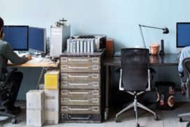 On either end of the photo, two developers work. A vintage filing cabinet sits between their desks.