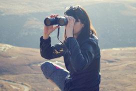 On a windswept hill a squatting woman peers through binoculars.