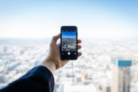 Business man holding mobile phone over a city skyline