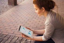 Outside on a brick patio, a young woman studies a dashboard on a tablet