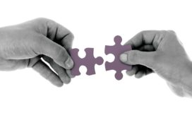 Black and white photo of hands fitting puzzle pieces together
