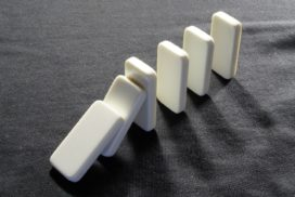 White dominoes on a dark gray cloth beginning to fall over