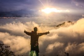 man looking down on clouds standing on a mountain with his thumbs up