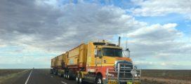 A semi trailer truck driving down a rural highway