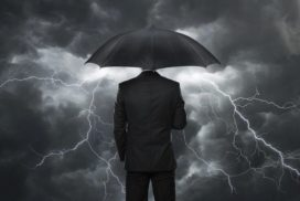 A businessman in a black suit holding a black umbrella stands in front of a gray-clouded sky while lightning explodes all around.