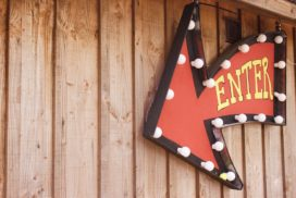 "A sign that reads ""Enter"" hangs on a wood paneled wall."