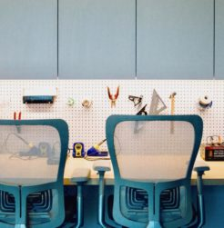 Office chairs sit in front of a work bench in a maker space. Tools hang on peg board.