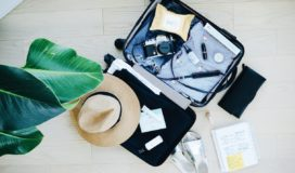 Open luggage filled with clothing, personal care products, a camera, and a hat lies on a parque floor. Sandals, a notebook, and a wallet lay next to it.